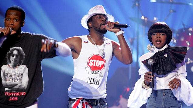 Deux hommes et une femme chantent dans des micros sur scène.