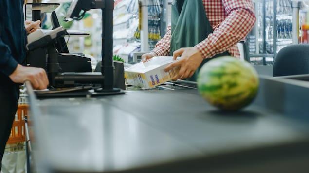 Un employé d'une épicerie scanne les achats d'un client, dont un melon d'eau.