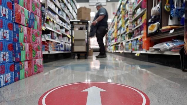 Un employé place des articles sur une tablette de l'épicerie.