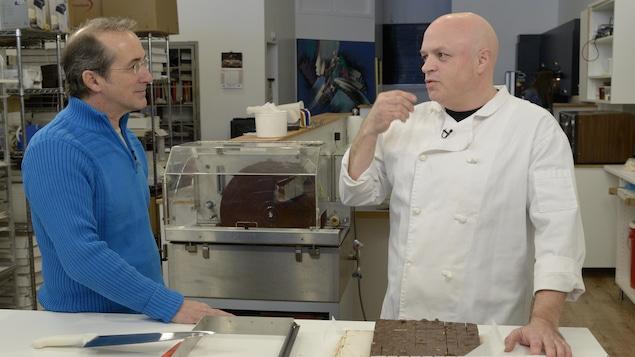 Denis Gagné et le André Schott debout face à face dans une cuisine avec des fudges sur le comptoir devant eux.