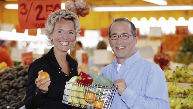 Animateurs côte à côte souriant dans un marché. Denis Gagné tient un mini panier de provisions dans ses mains.