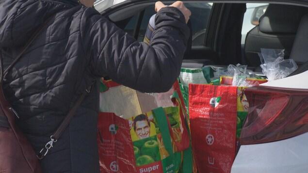Une femme dépose quelque chose dans les sacs d'épicerie réutilisable qui se trouvent dans le coffre de sa voiture.