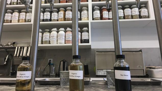 Des étagères avec des pots d'épices et trois distributeurs en fût à l'avant-plan avec trois bouteilles.