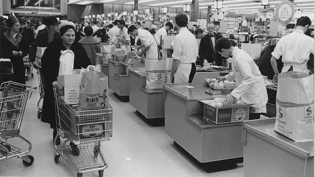 Une femme passe avec son panier d'épicerie rempli derrière la rangée de caisses d'un supermarché Steinberg.