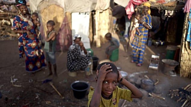 Un jeune garçon se tient la tête entre les mains.