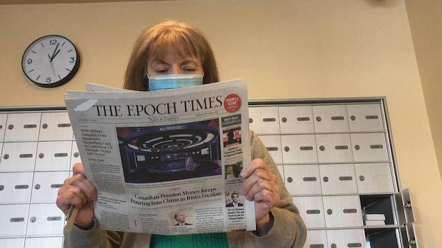 Une femme tient une copie du journal « The Epoch Times » devant une rangée de boîtes postales.