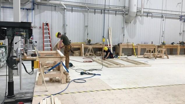 Deux jeunes hommes portant des casques de construction construisent un mur dans un atelier de formation professionnelle.
