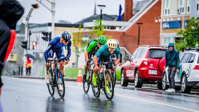 Quatre cyclistes roulent dans une rue mouillée. Une personne sur le côté crie pour les encourager.