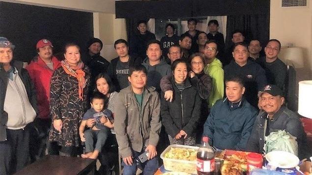 Environ 25 hommes, femmes et un enfant sont rassemblés dans une petite salle devant une table chargée de nourriture.