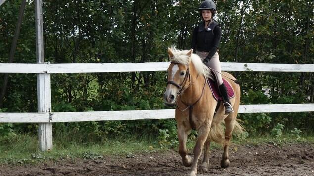 Sarah à cheval dans le terrain d'obstacles