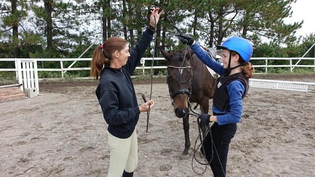 Les deux femmes manient de l'équipement devant un cheval.
