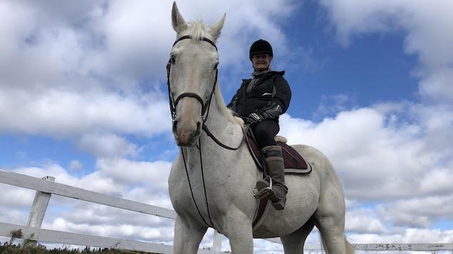 Pâquerette Santerre sur un cheval blanc.