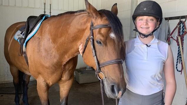 Sarah tient la têt de  son cheval.