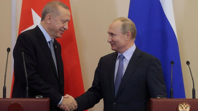 Recep Tayyip Erdogan et Vladimir Poutine se serrent la main.