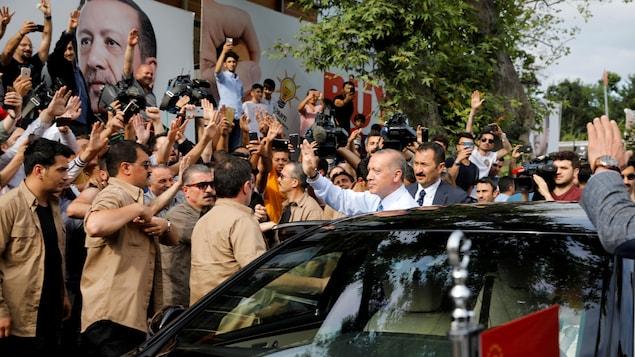 Erdogan se tient à côté de sa voiture entouré de gardes du corps et de gens qui le saluent.