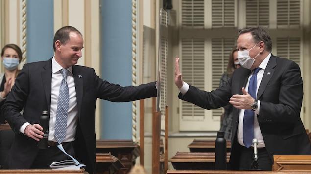 Eric Girard et François Legault posent une main sur un plexiglas, comme pour se donner une tape de félicitation.