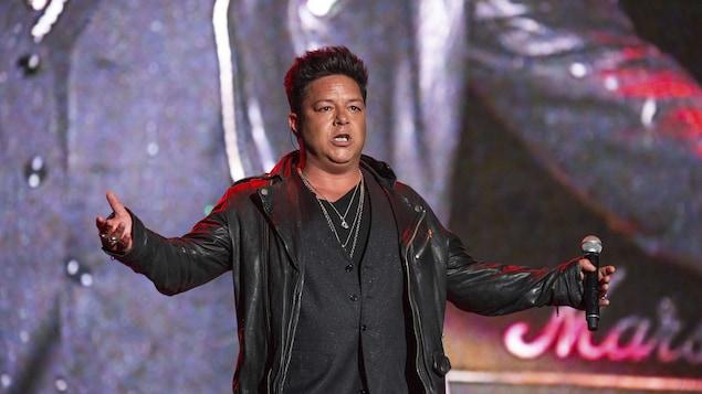 Le chanteur sur scène, micro à la main.