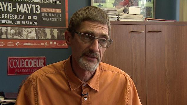 Un homme, qui porte une chemise orange et des lunettes, s'adresse à une journaliste.