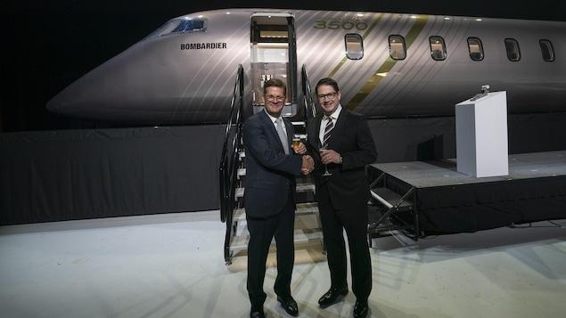 Éric Martel et Pierre Beaudoin se serrent la main devant une maquette d'avion.