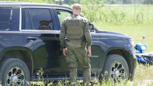 Un agent du de dos près d'un véhicule de police dans un milieu rural.