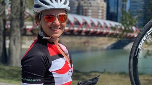 Erica Wiebe, casquée, tient son vélo du guidon des deux mains, et sourit.