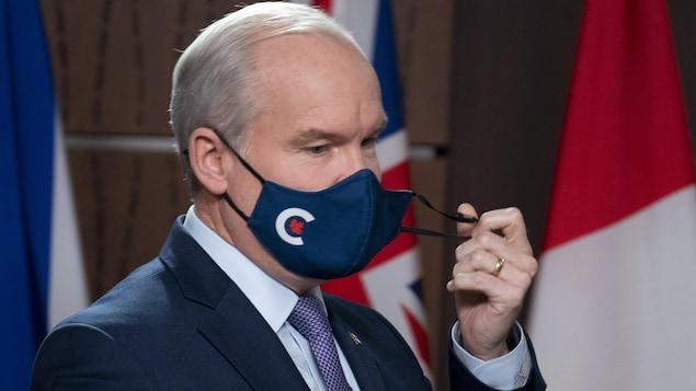 Devant les drapeaux du Canada et des provinces, Erin O'Toole ôte son masque portant le symbole du Parti conservateur du Canada.