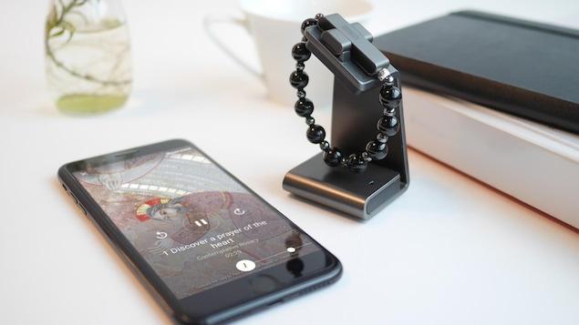 Un téléphone intelligent affiche une prière à côté du chapelet connecté.