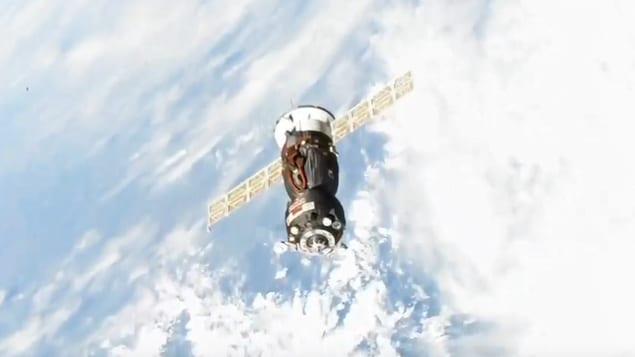 Un engin Soyouz flotte dans l'espace, devant la Terre.