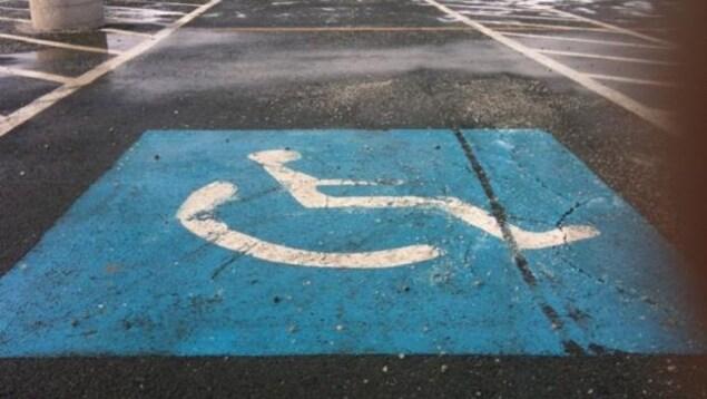 Photo du symbole pour personnes handicapées peint sur la chaussée dans un terrain de stationnement