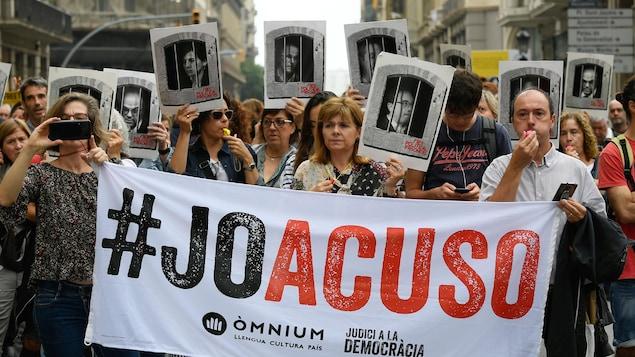 Des gens marchent et tiennent des photos des indépendantistes qui ont reçu des peines de prison.