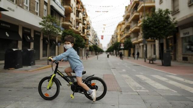 Un enfant à vélo traverse une rue.