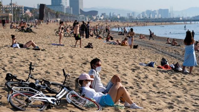 Des Espagnols profitent du soleil sur une plage de Barcelone.