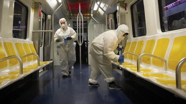 Des employés du métro nettoient un wagon de métro.