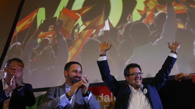 Deux hommes applaudissent alors qu'un autre lève les bras dans les airs devant un écran sur lequel est projeté des images d'un rassemblement politique en Espagne.
