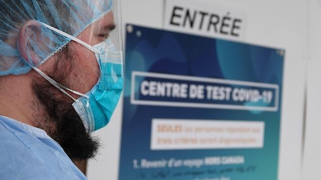 Un travailleur du milieu de la santé muni d'un masque de protection attend les citoyens au centre de test.