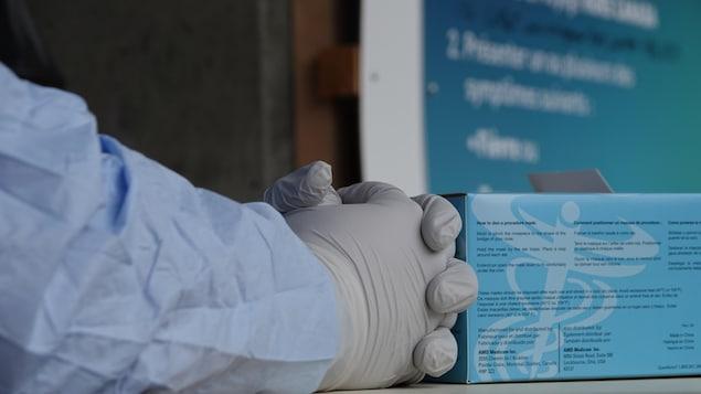 Un employé muni de gants de protection attend les citoyens au centre de dépistage de la COVID-19 à Sherbrooke.