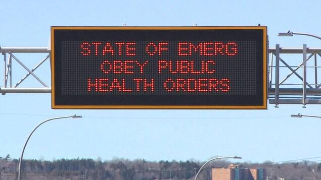 Panneau d'affichage numérique au-dessus d'une route annonçant l'état d'urgence.