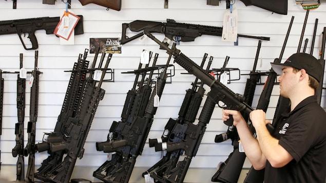 Un préposé nettoie un fusil AR-15 dans un magasin d'armes à feu.
