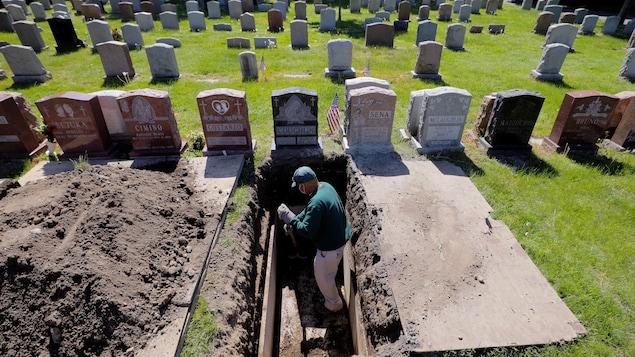 Un employé de pompes funèbres creuse une tombe dans un cimetière.