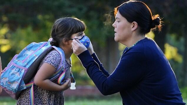 Une femme ajuste un couvre-visage sur le visage d'une fillette.