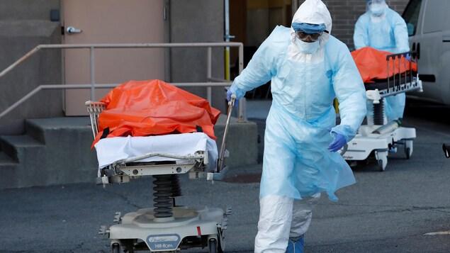 Un travailleur de la santé tire un lit d'hôpital sur lequel se trouve le corps d'une personne tuée par la COVID-19.