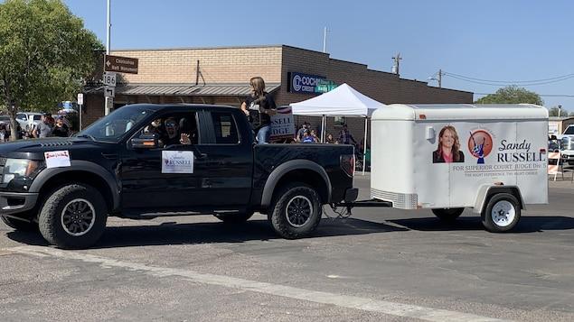 Une femme se tient debout dans la boîte d'un camion noir à grosses roues tirant une remorque sur laquelle apparaît la photo de la candidate et est inscrit : « Sandy Russell for Superior Court Judge ».