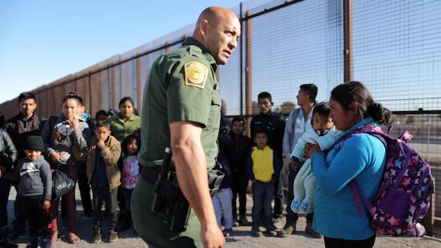Des gardes frontaliers interrogent des familles de migrants d'Amérique centrale à la frontière entre le Mexique et les États-Unis.