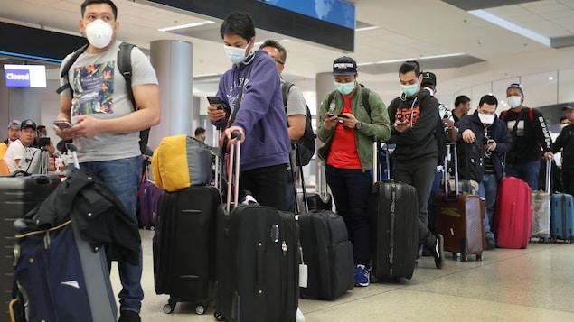 Des voyageurs en attente dans un corridor de l'aéroport international de Miami, en Floride.