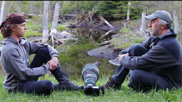 Antoine et Pierre Etcheverry  assis face à face dans la forêt.