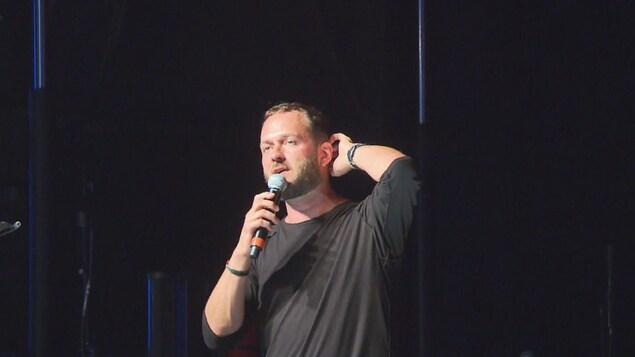 Un humoriste parle au micro en se grattant la tête.