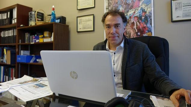 Etienne Vuillaume assis derrière son ordinateur dans le bureau du Gaboteur.