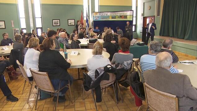 Présentation du maire devant un groupe.
