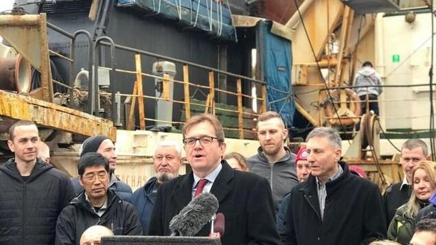 Un groupe de personnes associées à une expédition dans le golfe de l'Alaska rassemblé devant un navire alors que le ministre Jonathan Wilkinson prend la parole devant le public.