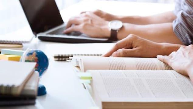 Des étudiants devant un ordinateur et un livre ouvert
